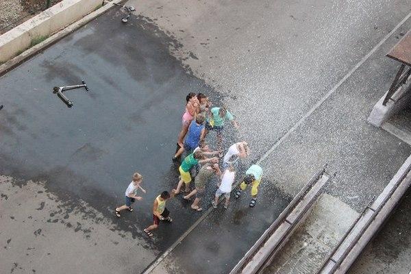 Летом, в жару, детей из окна поливают водой. Краснодар 2015.