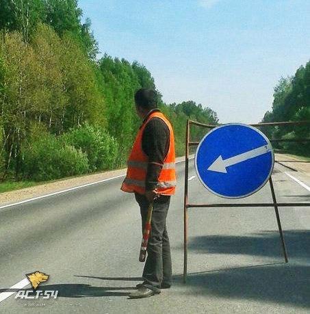 Суровый дорожный рабочий регулирует движение на ремонтном участке трассы Новосибирск - Томск при помощи бейсбольной биты.