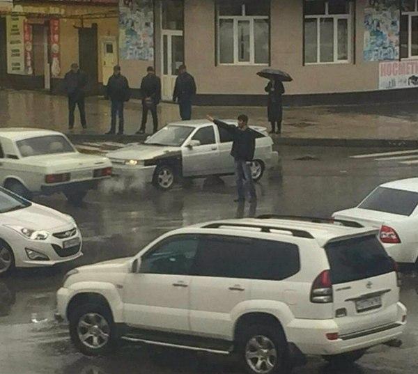 На перекрёстке не работает светофор, и двое мужчин в такую погоду долго стоят и помогают регулировать движение.