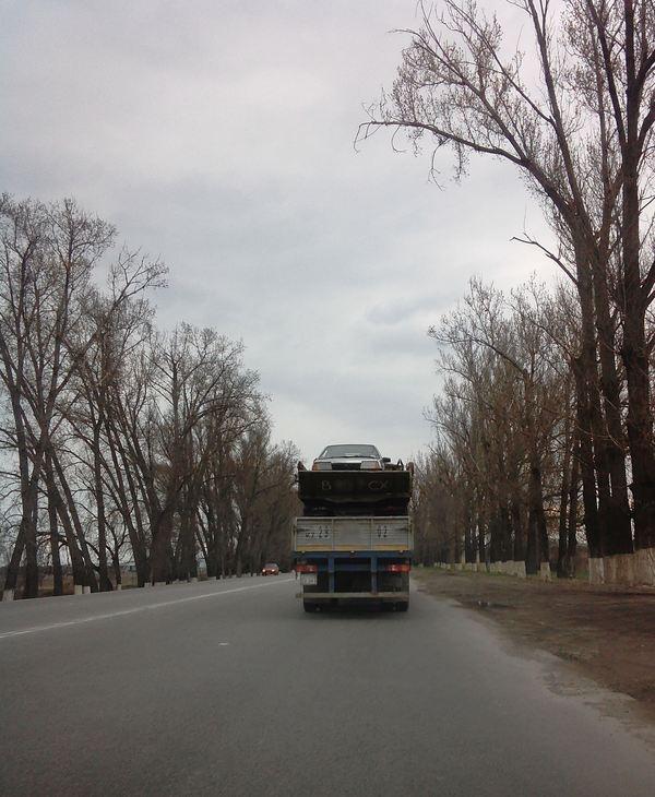Девятка в кузове грузовика на прицепе Камаза