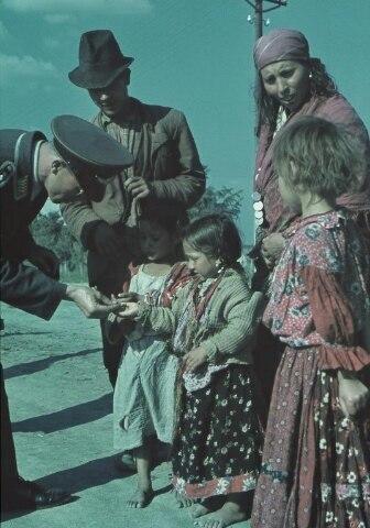 Оберфельдфебель люфтваффе дарит монетку цыганской девочке на острове Крит, Вторая мировая война.