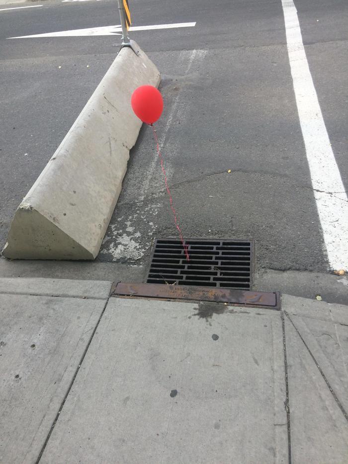 Кто-то привязывает красные воздушные шары к решетками канализации в  городе.