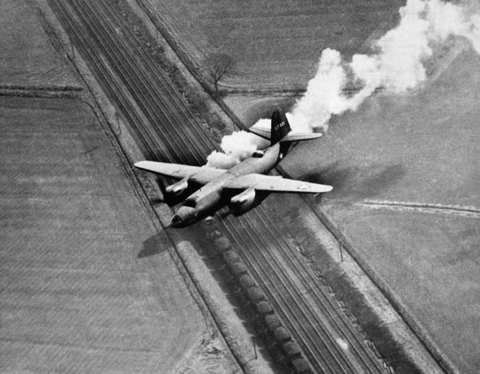 Американский бомбардировщик B-26 возвращается из боевого вылета, пролетая над железной дорогой на территории Великобритании. Авиация, Фотография, Самолет, Поезд, Оптические иллюзии